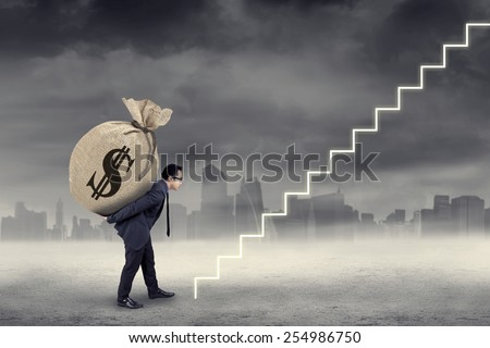 Young businessman walking on the stairs while carrying a money bag to the sky - stock photo