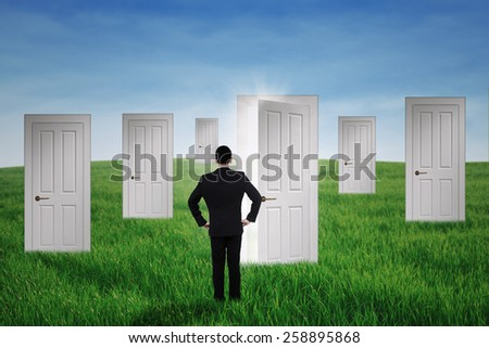 Young businessman walking to opportunity doors on the meadow