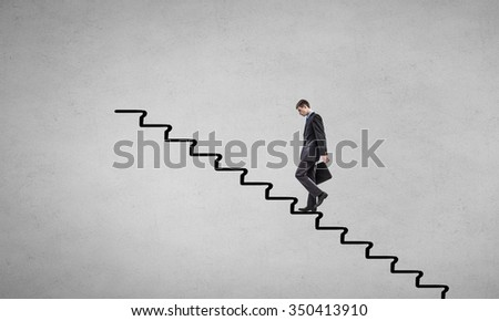 Young businessman walking up on ladder representing success concept - stock photo