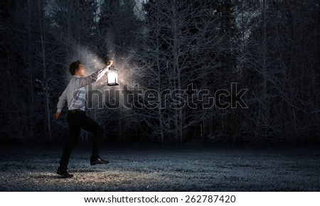 Young businessman walking with lantern in darkness - stock photo
