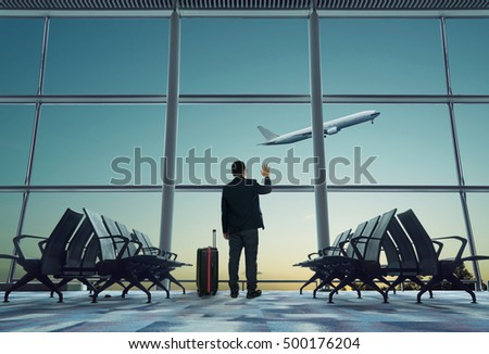 young businessman waving good bye at airport