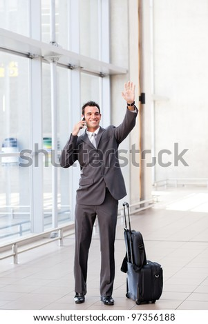 young businessman waving good bye at airport - stock photo