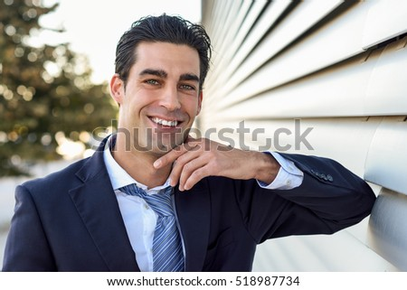 Young businessman wearing blue suit and tie in urban background. Man with formal clothes in the street. Blue eyes guy with toothy smile.