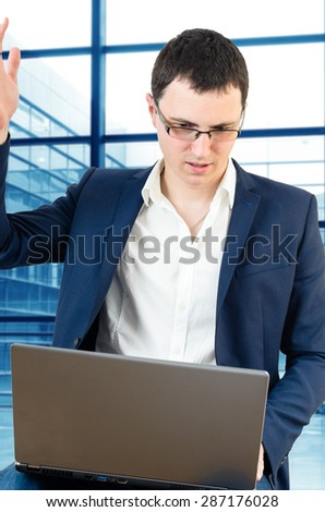 Young businessman wearing glasses and holding his head on the airport with laptop in his lap