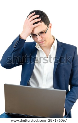 Young businessman wearing glasses and holding his head on the white backgroundt with laptop in his lap