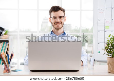Young businessman wearing glasses is in office full of folders for documents and office supplies. Businessman using laptop, smiling and looking at the camera  - stock photo