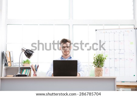 Young businessman wearing glasses is in office full of folders for documents and office supplies. Businessman using laptop - stock photo