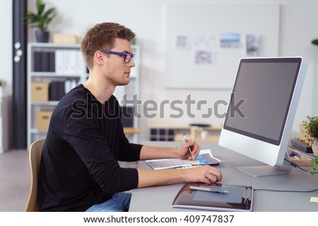 Young businessman wearing glasses sitting at his desk at the office working on a large desktop computer monitor, side view