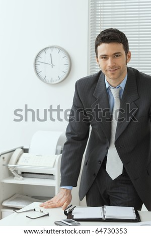 Young businessman wearing grey suit, standing behind office desk, smiling.? - stock photo