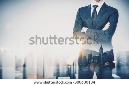 Young businessman wearing modern suit and standing with his arms crossed. Double exposure. Horizontal, contemporary city background - stock photo