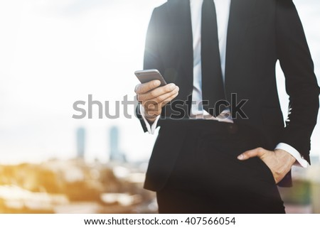Young businessman wearing modern suit and using smartphone outdoors, professional male employer using mobile phone while working at office, blurred background with copy space for content or design - stock photo