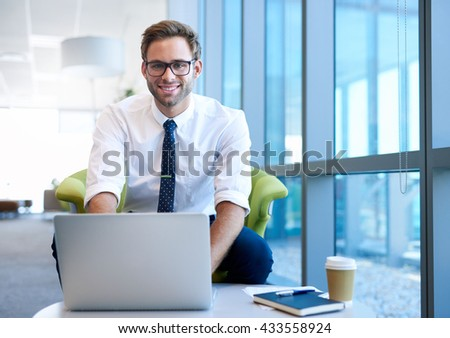 Young businessman wearing stylish spectacles, smiling at the camera while sitting in a modern office space, using his laptop - stock photo
