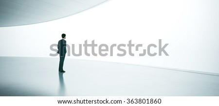 Young businessman wearing suit and stands in the open space interior - stock photo