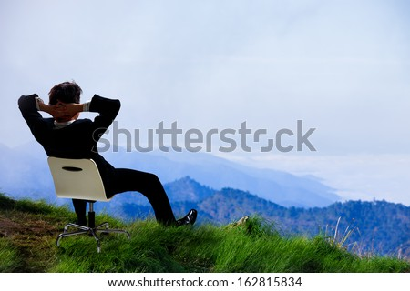 Young businessman who sits on a chair at the top of the mountain and looks into the sky - stock photo