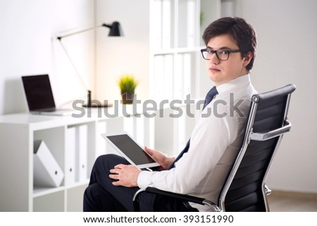 Young businessman wih tablet sitting on chair. Office at background. Concept of work.