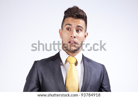 Young businessman with a fear expression on his face (isolated on gray) - stock photo