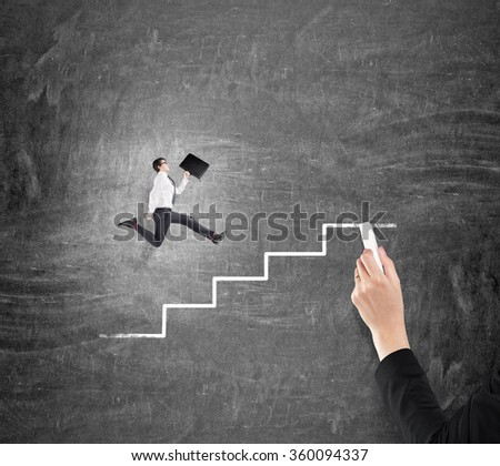 Young businessman with a folder running up a drawn stairs along a blackboard, hand drawing steps with a chalk. Concept of career growth.