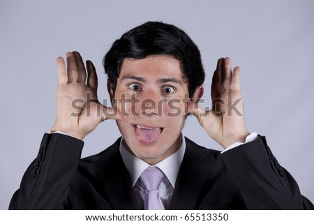 Young businessman with a funny face and his tongue out (isolated on gray) - stock photo