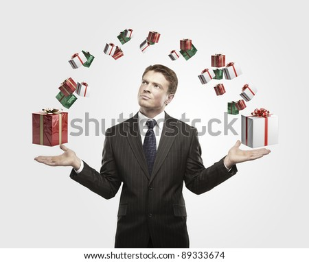 Young  businessman with a gift boxes in his hands. On a gray background.