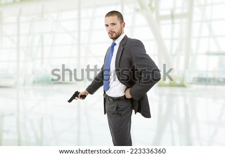 young businessman with a gun at the office - stock photo