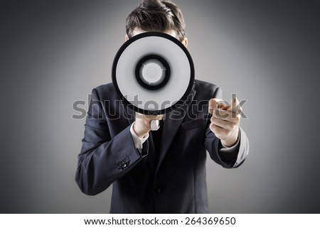 Young businessman with a megaphone - stock photo