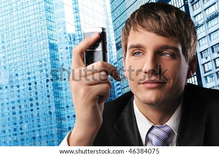 Young businessman with a mobile phone against his office building