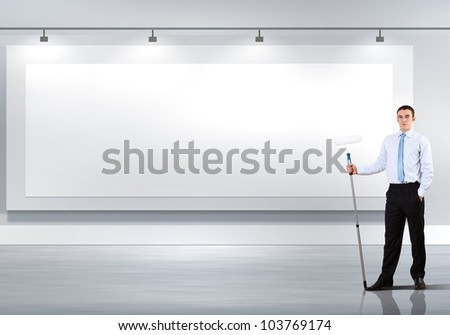 Young businessman with a paint brush against blank white wall - stock photo