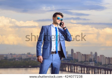 Young businessman with a phone in his hand, he is dressed in a blue suit. He stands against the backdrop of a beautiful, textured sky with clouds and the city.