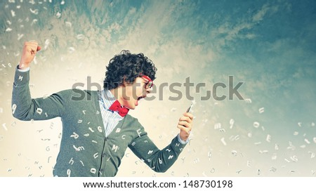 Young businessman with a red tie shouting furiously at his mobile phone - stock photo