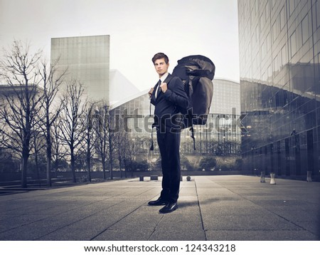 Young businessman with a travel backpack in a city - stock photo