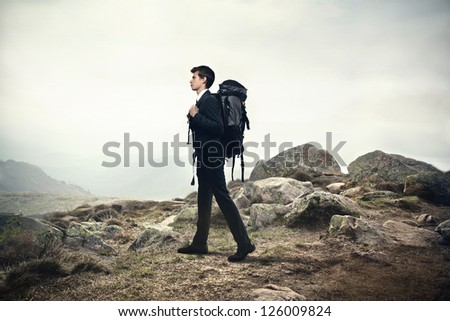 Young businessman with a travel backpack walking on a hill