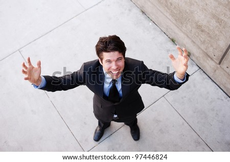 Young businessman with arms open celebrating