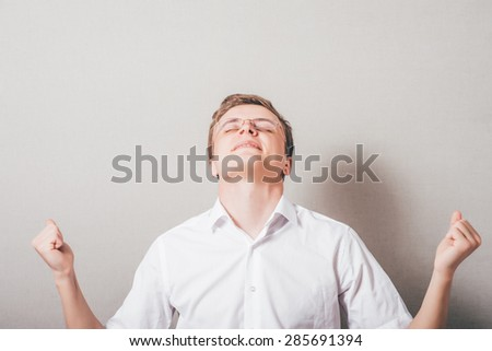 Young businessman with arms outstretched celebrating success  - stock photo