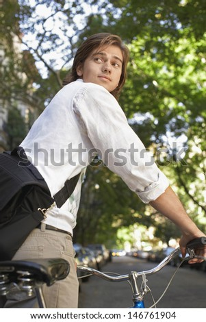 Young businessman with bicycle looking over shoulder on city street - stock photo