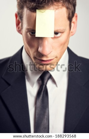 Young businessman with blank note on his forehead. - stock photo