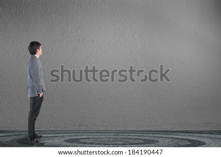 Young businessman with blank wall