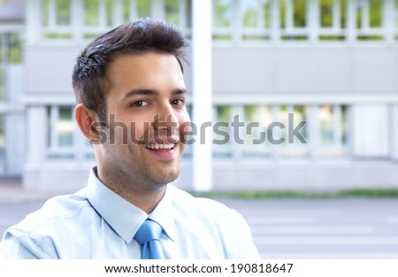 Young businessman with blue tie laughing at camera