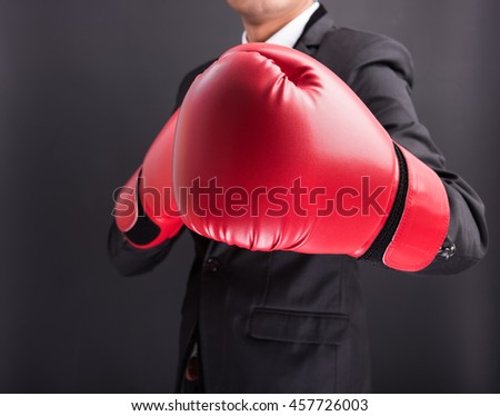 Young businessman with boxing gloves isolated on black background