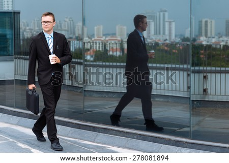 Young businessman with briefcase and coffee cup walking outdoors - stock photo