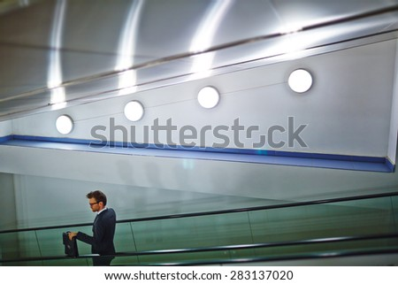 Young businessman with briefcase moving downstairs on escalator - stock photo