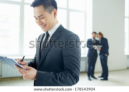 Young businessman with clipboard writing plan in working environment - stock photo