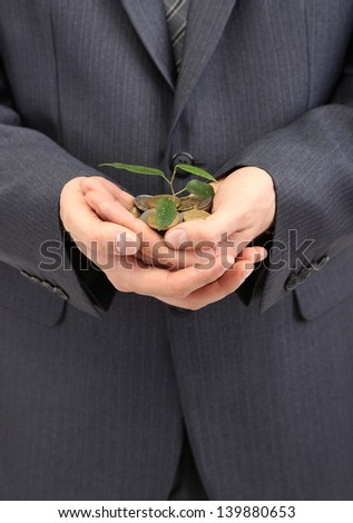 Young businessman with coins and plant isolated on white