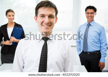 Young businessman with colleagues in the background