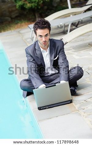 Young Businessman with Computer next to Swimming Pool - stock photo
