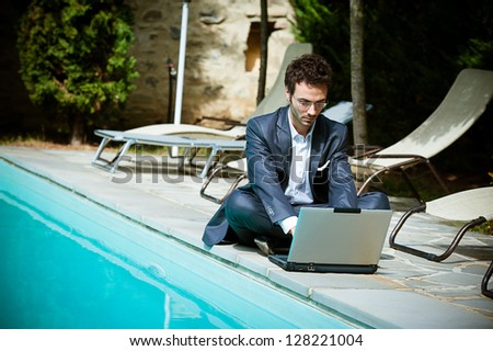 Young Businessman with Computer next to Swimming Pool Italy - stock photo