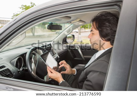 Young Businessman with Digital Tablet on car