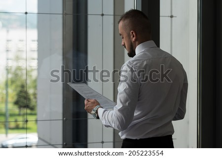 Young Businessman With Document At Office