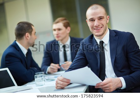 Young businessman with document looking at camera in working environment - stock photo