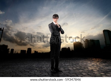 Young businessman with doubtful expression and cityscape on the background