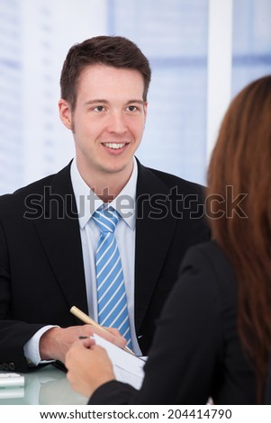 Young businessman with female colleague in meeting at office desk - stock photo